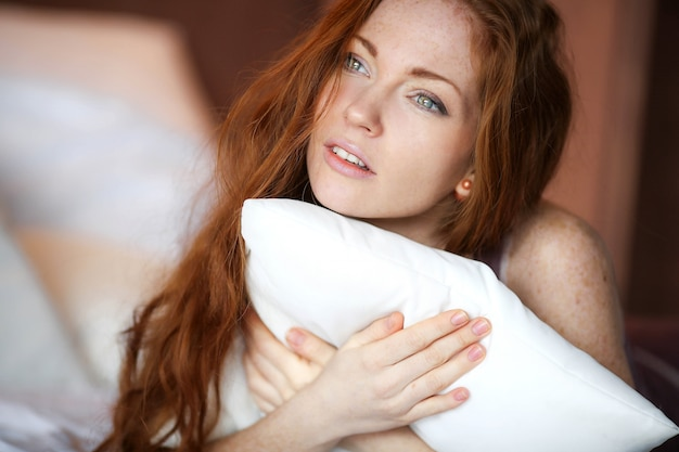 Morning in bed, a young charming red-haired woman with freckles lying in bed