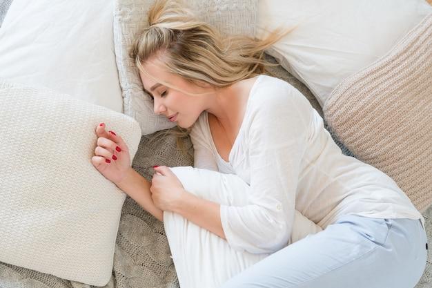 Утром перед сном. концепция отдыха и релаксации. молодая блондинка мирно спит в постели, обнимая подушку.