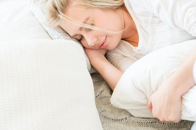 Утром перед сном. концепция отдыха и релаксации. молодая блондинка мирно спит в постели.