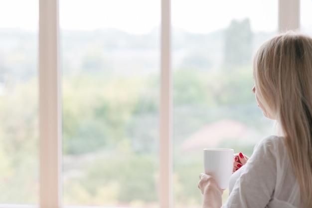 Утренний напиток. женщина смотрит через окно и держит чашку белого горячего напитка.
