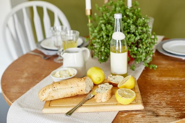 朝の朝食パンとバター、レモネードとレモン。女性がパンにバターを塗る。夏の日の窓に太陽が輝いています