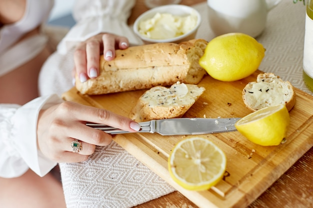 朝の朝食パンとバター、レモネードとレモン。女性がパンにバターを塗る