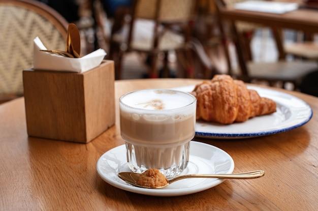 朝の朝食コーヒーラテとカフェの背景にチョコレートクロワッサン