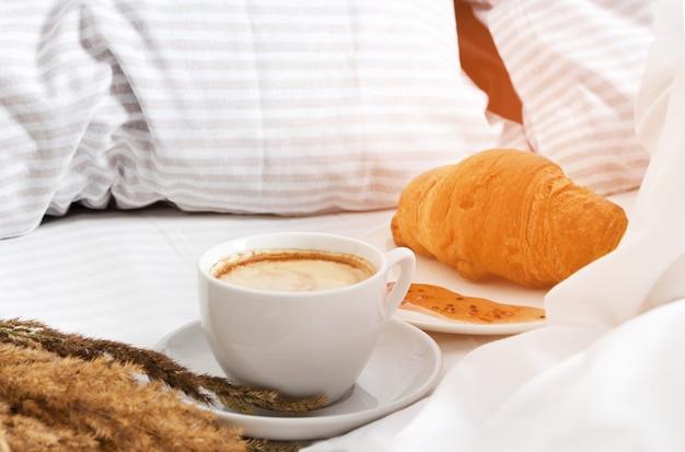 ベッドでの朝の朝食。白い背景の上のクロワッサルとコーヒーのカップ