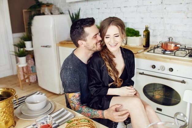 キッチンで朝の朝食を愛するカップル。男と女が抱きしめ、パンとチーズを切る。愛するカップルの顔に喜びと笑顔