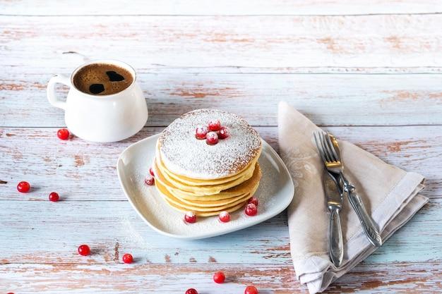木製のテーブルとコーヒー1杯にクランベリーと粉砂糖を添えたパンケーキの朝の朝食。