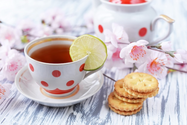 Утренний завтрак с чаем в чашке разноцветного горошка с печеньем
