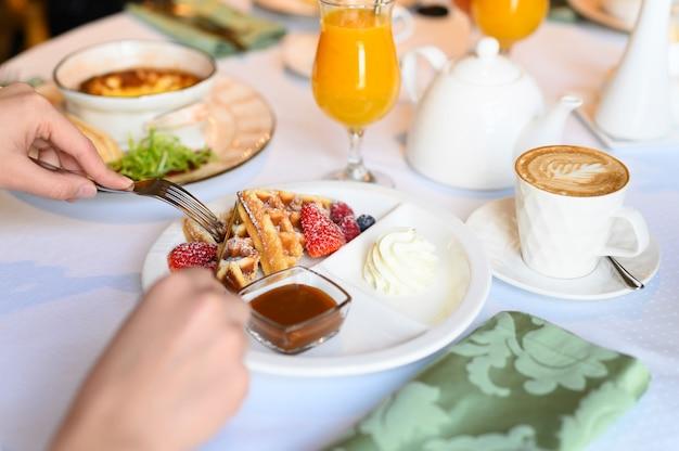 朝はレストランで朝食またはブランチをお楽しみください。飲み物と食べ物のテーブル。女性の手がナイフとフォークでウィーンのワッフルをカットしました。セレクティブフォーカス Premium写真
