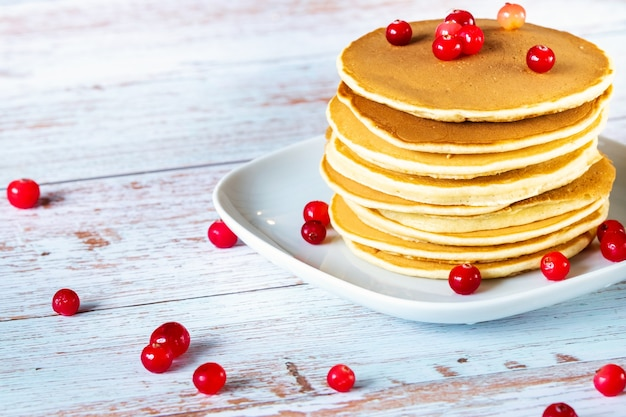 プレートの木製テーブルにクランベリーと朝の朝食のパンケーキ。