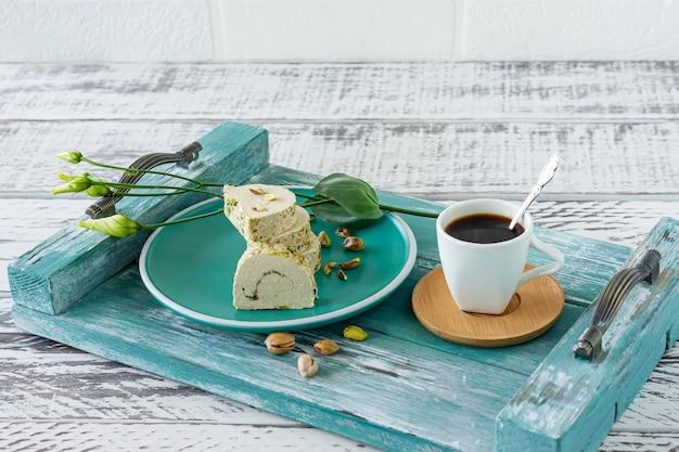 아침 조식 - 꽃이 든 푸른 나무 쟁반에 커피 한 잔을 곁들인 얇게 썬 피스타치오 할바.