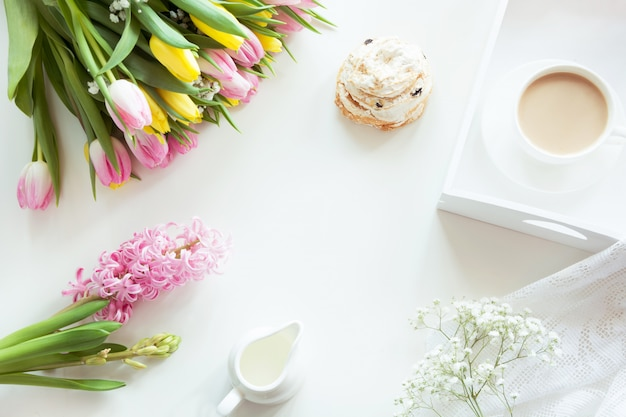 Morning breakfast in spring with a cup of black coffee with milk and pastries in the pastel colors