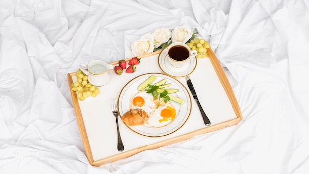 Morning breakfast tray on crumpled bed sheet