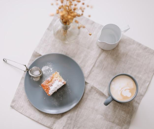 Утренний завтрак с кувшином для свежего домашнего торта и чашкой кофе на столе