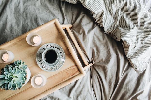 ベッドでコーヒーと朝の朝食。フラットレイ、トップビューライフスタイル静物構成。木製トレイとグレーのリネン。