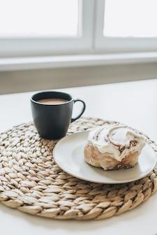 Утренний завтрак с кофе с молоком и пирожным на белом столе
