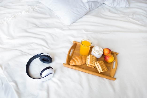 Morning breakfast with croissant and coffee on the white bed
