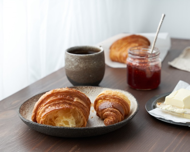 Morning breakfast with croissant on plate, cup of coffee, jam and butter. dark table by window