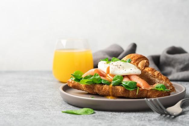 Утренний завтрак с круассаном, лососем, шпинатом и яйцом пашот