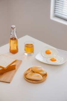 차 한 잔, 토스트, 계란 후라이, 빵을 식탁에 올려 놓은 아침 조식