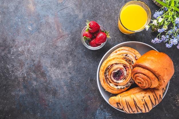 オレンジジュース、イチゴ、ロールパンで朝の朝食。トップビュー、テキストスペース