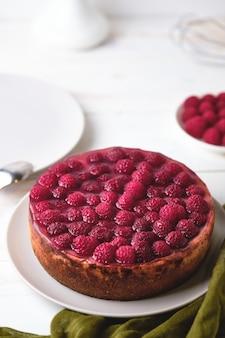 Утренний завтрак с малиновым чизкейком. десерт тарелку на белом деревянном столе.