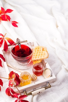 Morning breakfast with red tea, honey and waffles on a bed