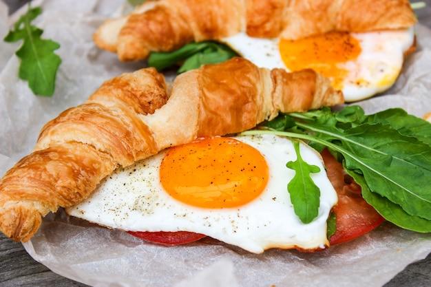 スクランブルエッグ、クロワッサン、ルコラの朝の朝食