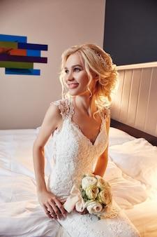 아침 신부. 그녀의 손에 꽃다발을 들고 하얀 웨딩 드레스에 여자. 결혼식을 준비하는 아름다운 금발 소녀