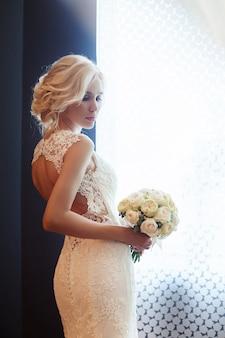 朝の花嫁。彼女の手に花束を持っている白いウェディングドレスの女性。結婚式の準備をしている美しいブロンドの女の子
