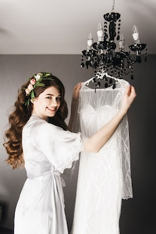 Morning of the bride. beautiful portrait of a bride in a peignoir with hair curls and fresh flowers near the wedding dress.