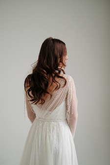 Morning of the bride. the bride is standing back, studio, white background