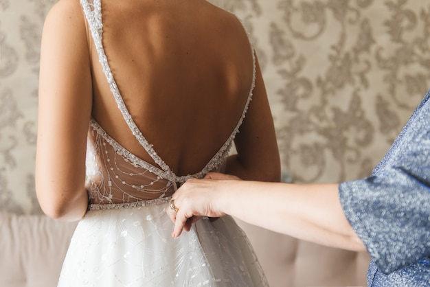 Morning bride. bridesmaid helping the bride lacing up her dress. girlfriends help the bride to fasten a dress