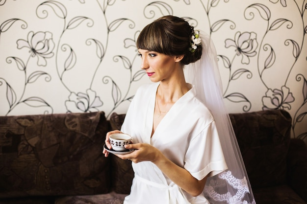 Morning of the bride. girl drinks coffee from a white cup. wedding ceremony