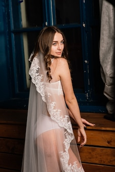 Morning of the bride. portrait of a beautiful young woman in a white underwear and a peignoir.