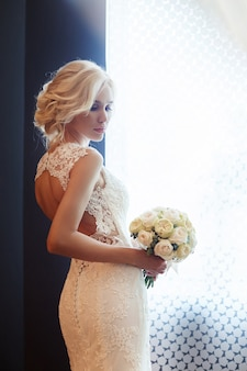 Morning bride. a woman in a white wedding dress holding a bouquet of flowers in her hands. beautiful blonde girl getting ready for wedding ceremony