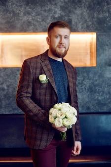 朝の花婿。彼の最愛の人のために花束を持っているジャケットを着た流行に敏感な男。結婚式の準備をしている美しいひげを生やした男