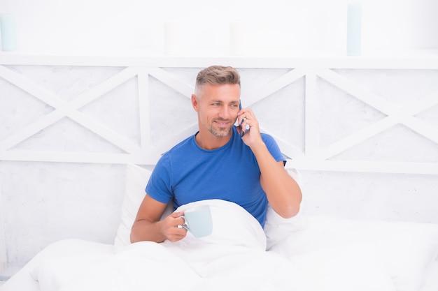 モーニングコール。モバイル会話。携帯電話。通信携帯電話。新鮮なニュースのコンセプト。おはようございます。一杯のコーヒーと一緒に家でリラックスする男のパジャマ。リモートワークのコンセプト。週末の休息。