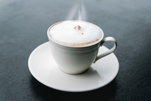 Morning cappuccino coffee on a black table