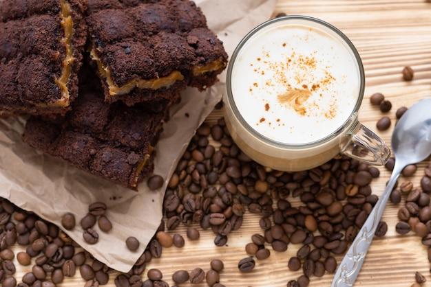 초콜릿 케이크와 함께 아침 카푸치노. 원두 커피와 나무 테이블에.