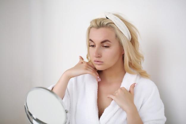 Утренний уход, молодая девушка в халате и с белым полотенцем пользуется кремом для тела.