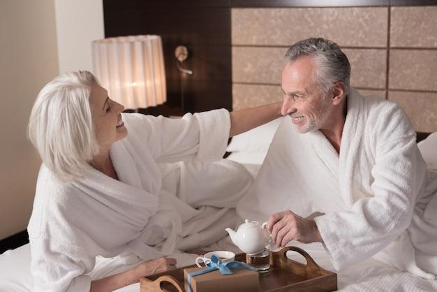 아침. 쾌활한 행복 세 커플 침대에 누워 기쁨을 표현하면서 아침을 먹고