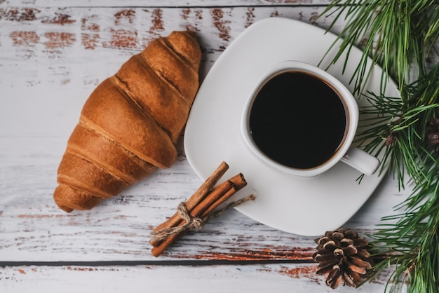 Morning christmas breakfast with a cup of coffee, croissant, cinnamon sticks
