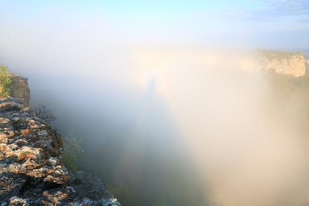 Mangup kale(ウクライナ、クリミア半島の歴史的な要塞と古代の洞窟集落)の頂上からの朝の曇りの景色とハローのある雲の上の影
