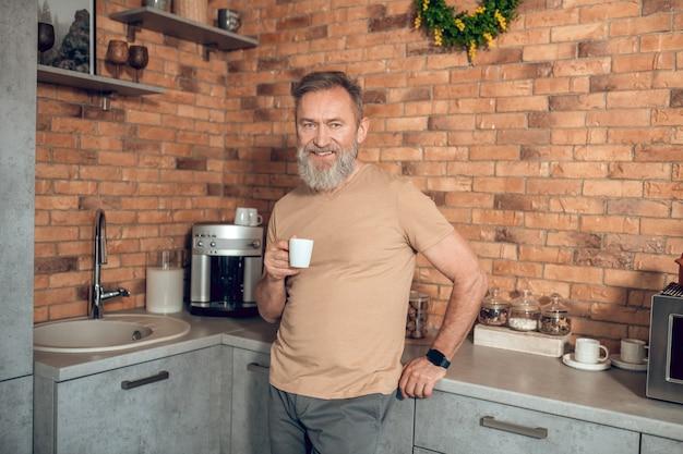 Утренний кофе. мидагедмен стоит на кухне с чашкой кофе в руках