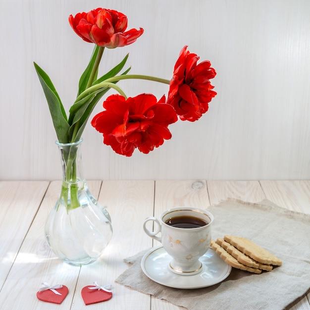 モーニングコーヒーと木製のテーブルにチューリップの花束。
