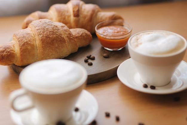 木製のテーブルに朝のコーヒーとクロワッサン。焼きたてのクリオサントとカプチーノ。木の板に空のクロワッサン。アプリコットジャム