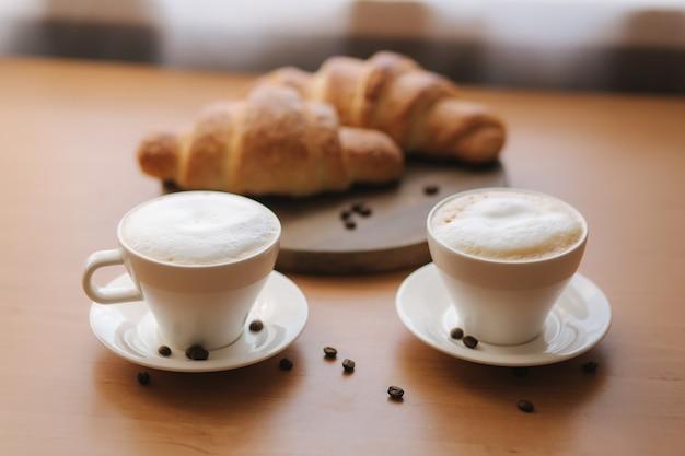 木製のテーブルに朝のコーヒーとクロワッサン。焼きたてのクリオサントとカプチーノ。木の板に空のクロワッサン