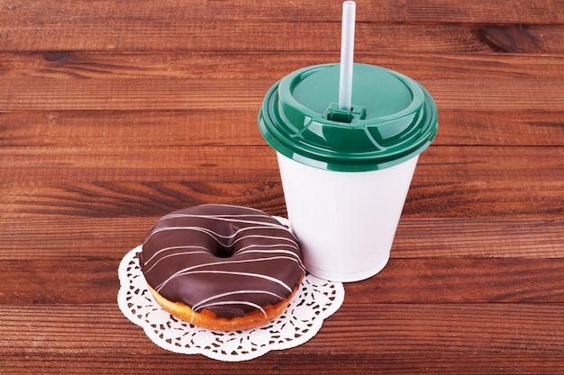 朝-チョコレートで満たされたコーヒーと自家製ドーナツ、木製のテーブルにドーナツの袋