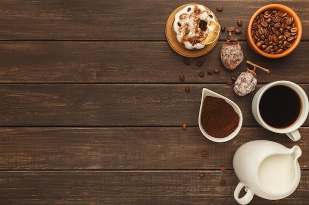 朝のコーヒーの背景。苦いアメリカーノ、挽いた豆、ミルクジャー、干し柿と素朴な木製のテーブルの上の小さなケーキのカップの境界線、コピースペース、上面図