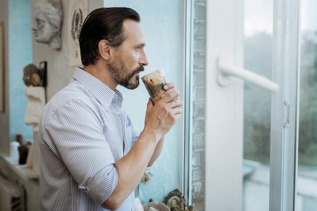 モーニング・コーヒー。仕事に行く前に朝のコーヒーを飲みながら窓の近くに立っているひげを生やした男